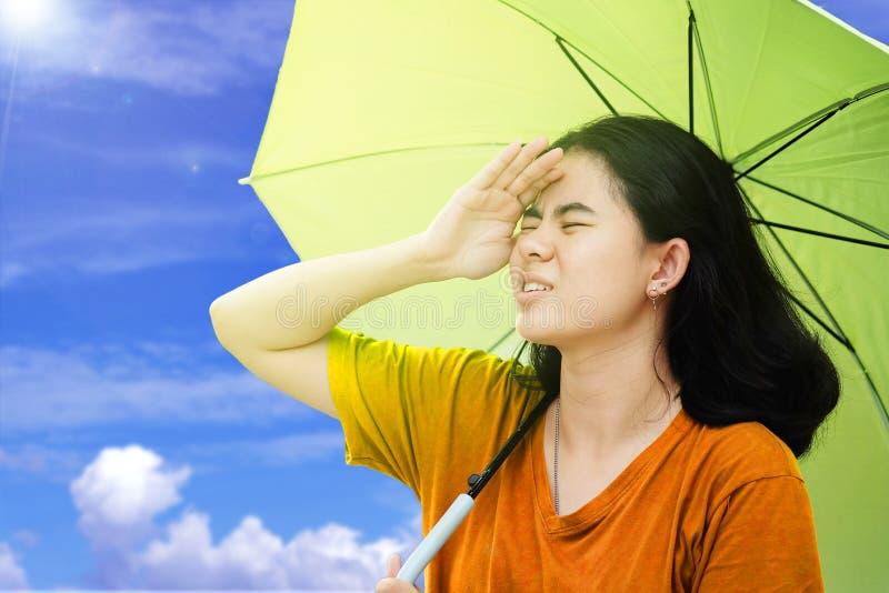 逗人喜爱的亚裔妇女使用他们的手到盖子她的从太阳的面孔和有阳光和天空蔚蓝和云彩backgro的举行伞 图库摄影