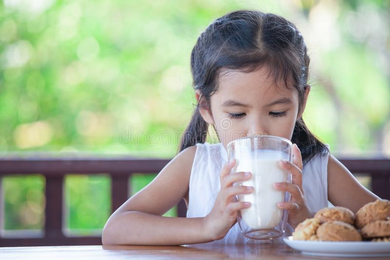 逗人喜爱的亚裔小孩女孩喝从玻璃的牛奶 库存图片