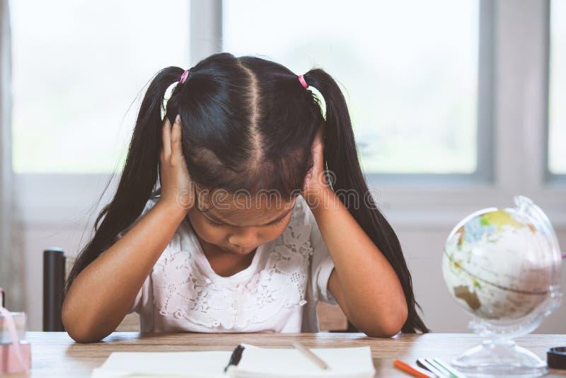 逗人喜爱的亚裔小孩女孩强调说并且疲倦了,当做她的家庭作业时 免版税库存照片