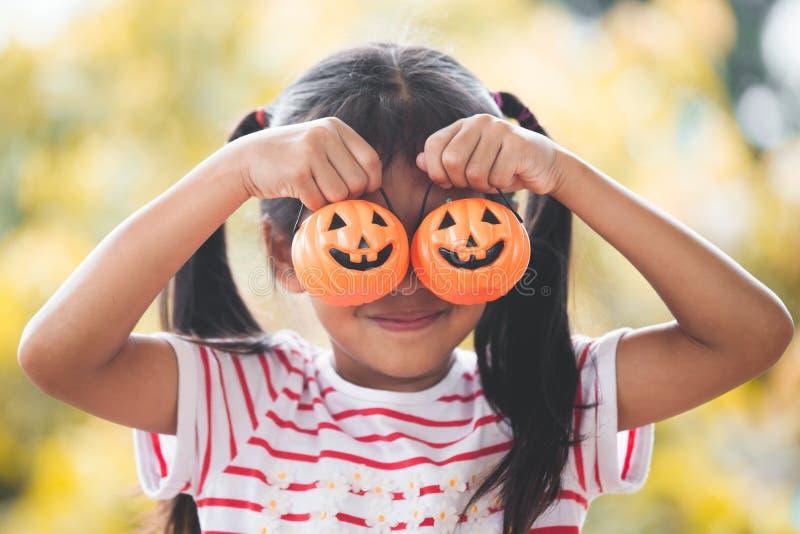 逗人喜爱的亚裔小孩女孩用桶南瓜 免版税库存图片