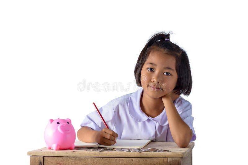 逗人喜爱的亚裔村姑记录下来收入收据和硬币与被隔绝的存钱罐在白色背景 免版税库存图片