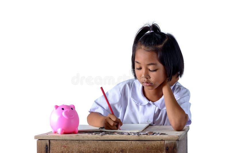 逗人喜爱的亚裔村姑记录下来收入收据和硬币与被隔绝的存钱罐在白色背景 库存图片