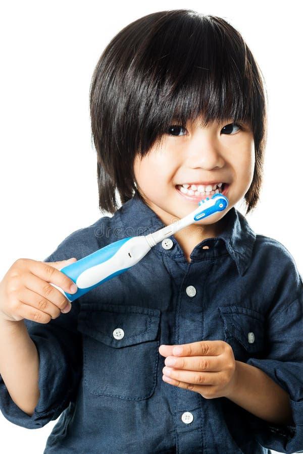 逗人喜爱的亚裔男孩掠过的牙 库存照片