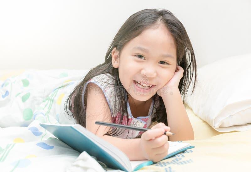 逗人喜爱的亚洲女孩微笑和文字对日志在床上 免版税库存照片