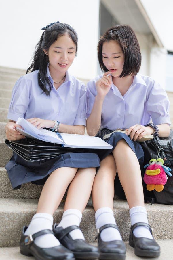 逗人喜爱的亚洲泰国高女小学生学生夫妇读书在学校 免版税库存照片