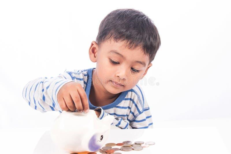 逗人喜爱的亚洲男孩挽救金钱 免版税库存图片