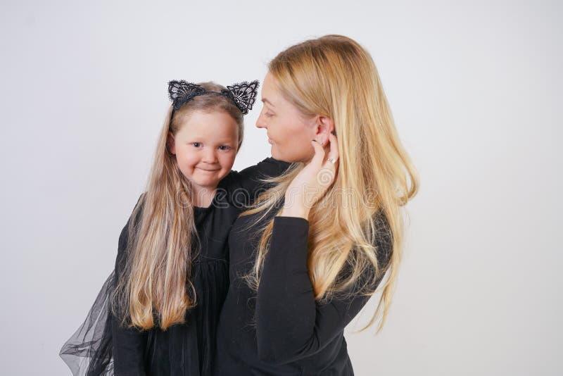 逗人喜爱的亲切的白种人白肤金发的摆在白色背景的妈妈和女儿 父母和儿童经验爱和拥抱 库存图片