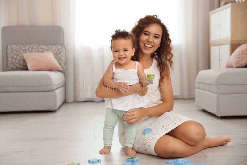 逗人喜爱的使用在地板上的婴孩和母亲 图库摄影