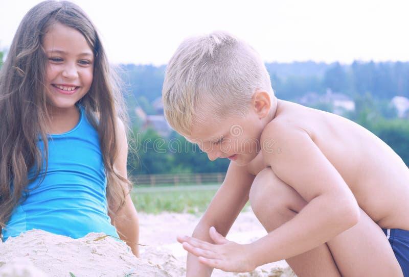 逗人喜爱的使用在海滩的小男孩和女孩 E 免版税库存图片