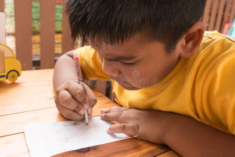 逗人喜爱的做在桌上的儿童小男孩家庭作业 库存图片
