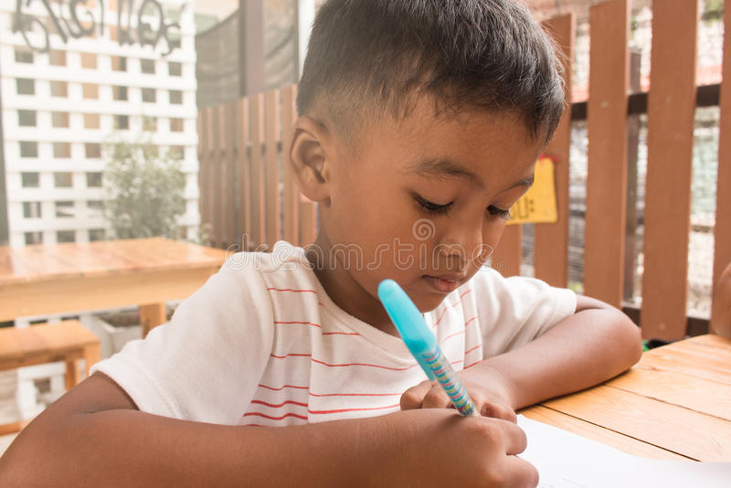 逗人喜爱的做家庭作业的儿童亚裔小男孩 免版税库存图片
