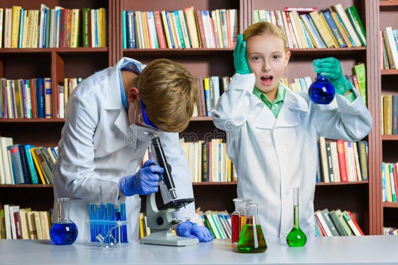 逗人喜爱的做生化研究的男孩和女孩  免版税库存照片