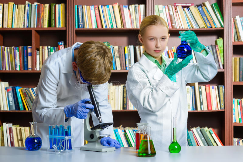逗人喜爱的做生化研究的男孩和女孩  免版税库存图片