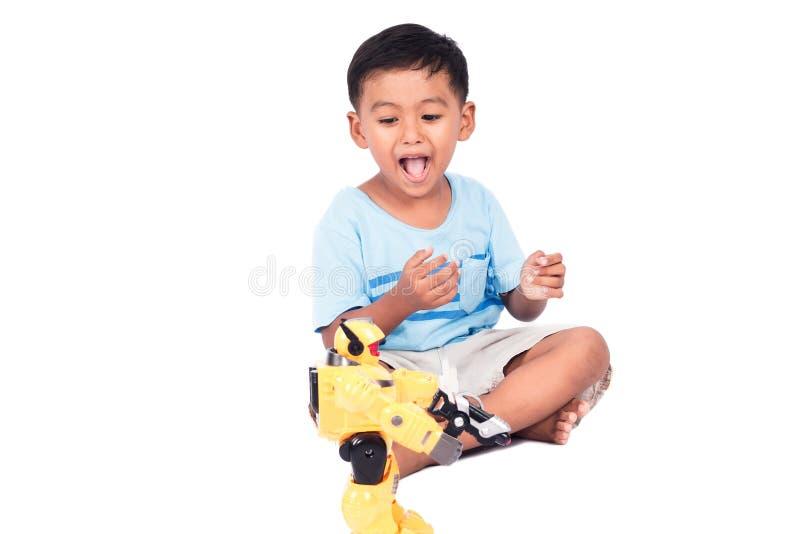 逗人喜爱的儿童亚洲小男孩戏剧机器人战斗的玩具 库存照片