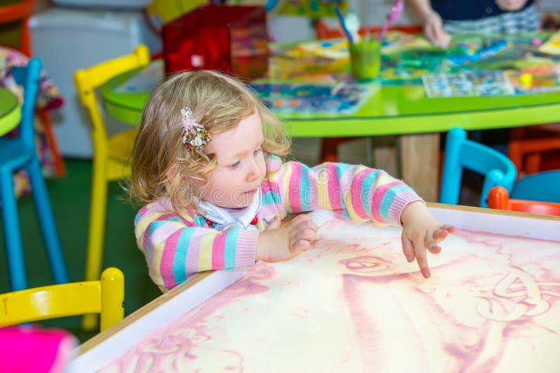 逗人喜爱的儿童女孩图画画在幼儿园的开发的沙子在桌上在幼儿园 免版税库存图片