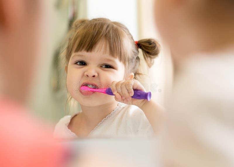 逗人喜爱的儿童女孩掠过的牙和看在镜子在卫生间里 图库摄影