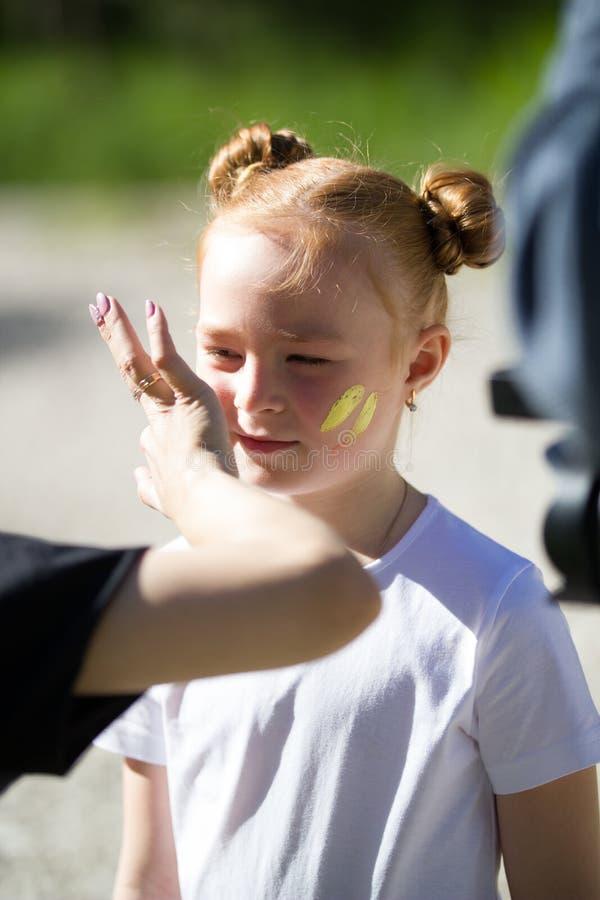 逗人喜爱的儿童女孩画象有被绘的面孔的谈话与她的朋友户外在夏日 免版税图库摄影