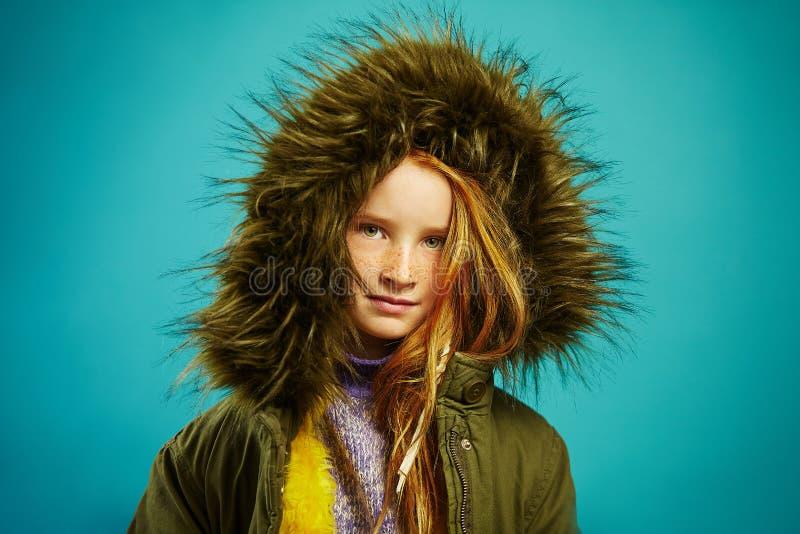 逗人喜爱的儿童女孩画象穿有敞篷的时髦的夹克在蓝色背景 免版税库存照片
