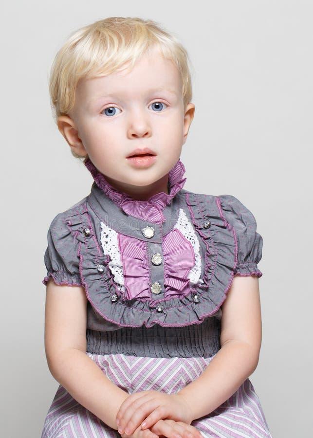 逗人喜爱的儿童小孩女孩特写镜头画象有金发和蓝眼睛的在摆在坐的葡萄酒减速火箭的维多利亚女王时代的哥特式礼服 免版税库存照片