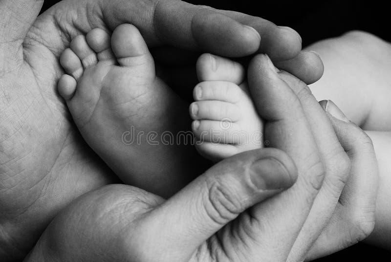 逗人喜爱的儿童小宝贝一点脚在父亲手上 古典特写镜头射击了关于家庭价值观并且做父母儿童儿童爱 免版税库存照片