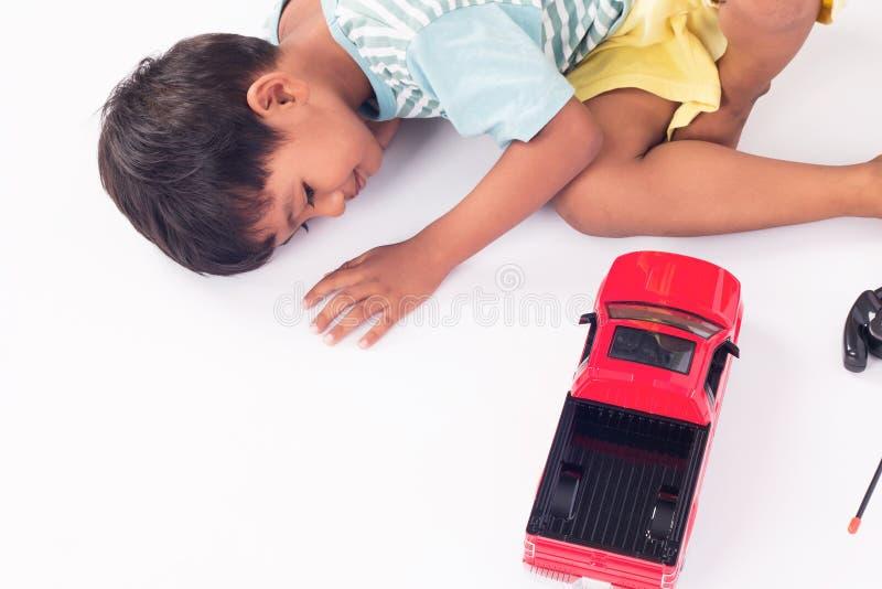 逗人喜爱的儿童小男孩说谎的戏剧玩具汽车 免版税图库摄影