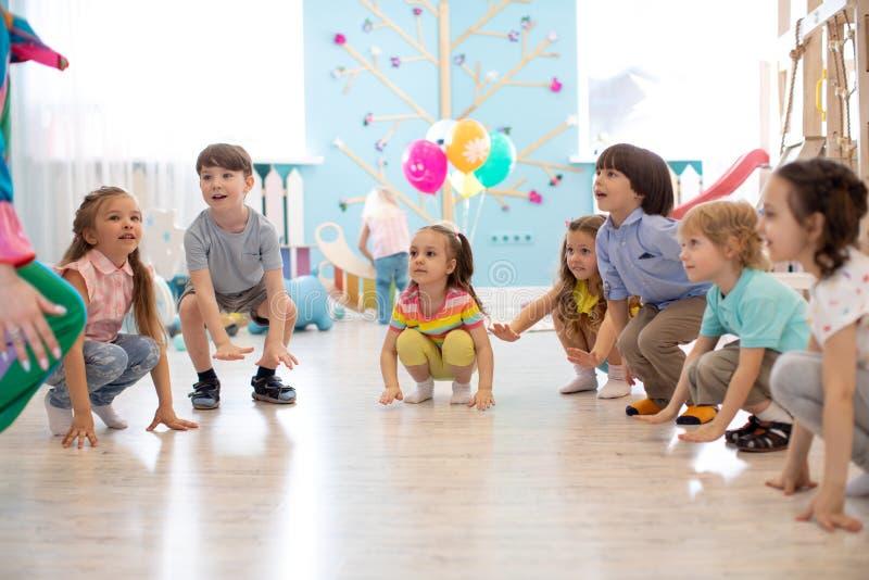 逗人喜爱的儿童男孩和女孩蹲演奏反复的小调 免版税图库摄影