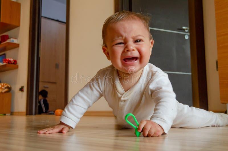 逗人喜爱的六个月哭泣的男婴有在地板上的肚子时间和的注意 免版税库存图片
