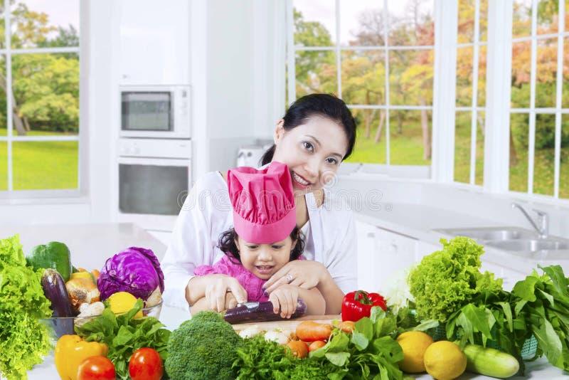 逗人喜爱的准备菜的女孩和母亲 免版税库存图片