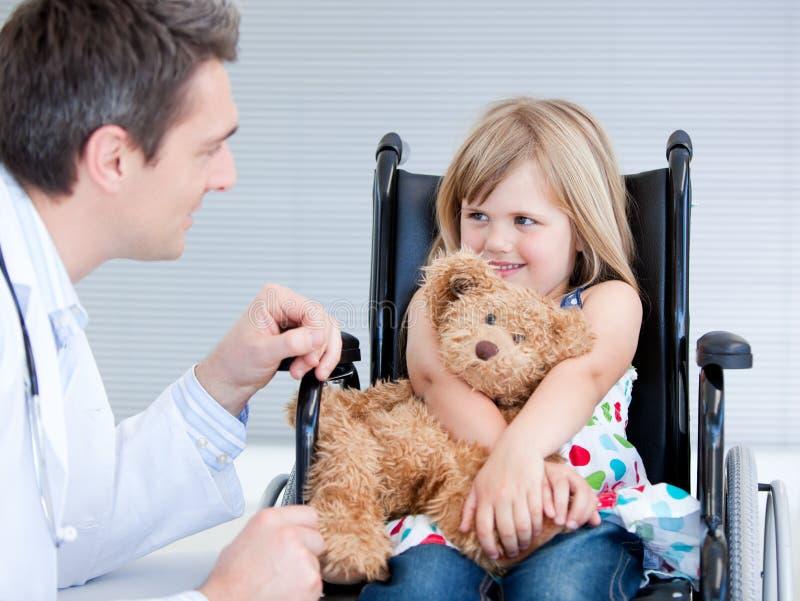 逗人喜爱的医生女孩她告诉与轮椅 免版税库存照片