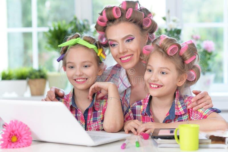 逗人喜爱的双女孩和母亲有坐在桌上的卷发夹的 库存照片