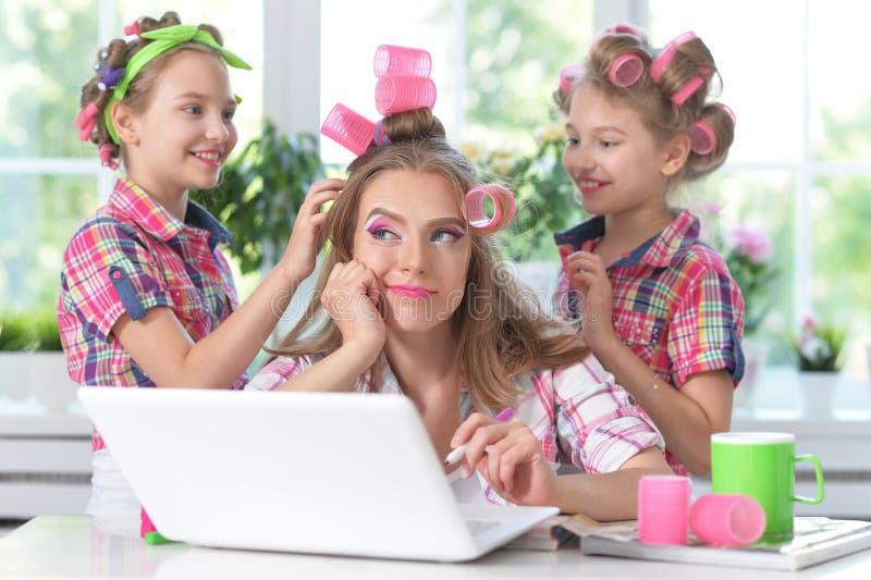 逗人喜爱的双女孩和母亲有坐在桌上的卷发夹的 库存图片