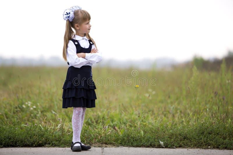 逗人喜爱的可爱的严肃的体贴的第一个平地机女孩和在长的金发的白色弓全长画象校服的 免版税库存照片