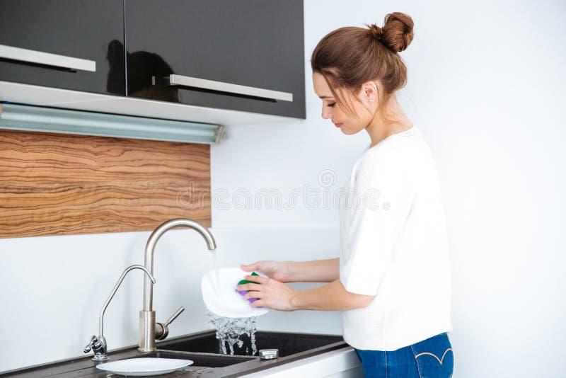 逗人喜爱的可爱的妇女站立的和洗涤的盘 库存图片