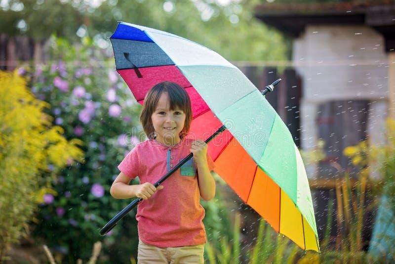 逗人喜爱的可爱的孩子,男孩,使用与五颜六色的伞在s下 免版税图库摄影