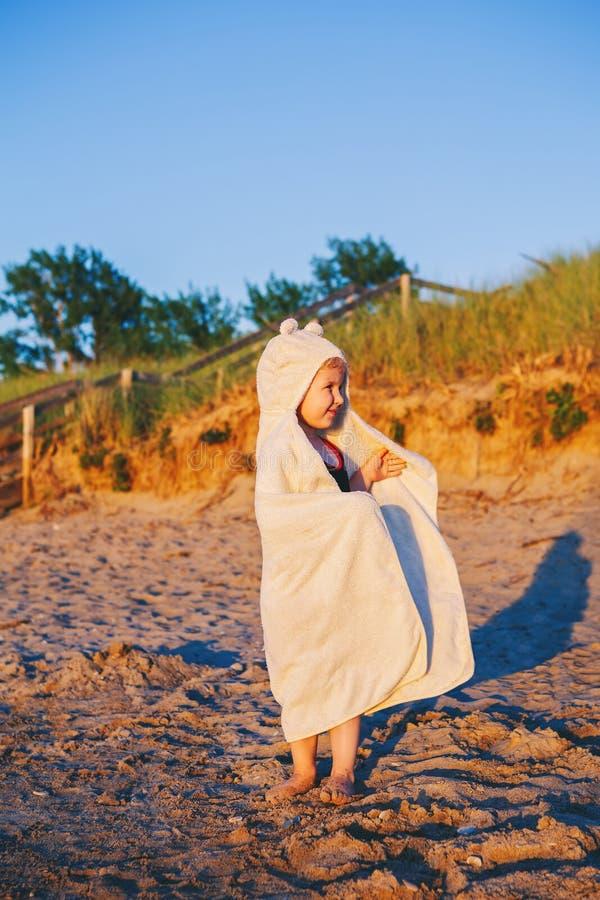逗人喜爱的可爱的愉快的微笑的小孩小女孩画象有毛巾的在沙丘铺沙获得石渣的海滩乐趣 免版税图库摄影