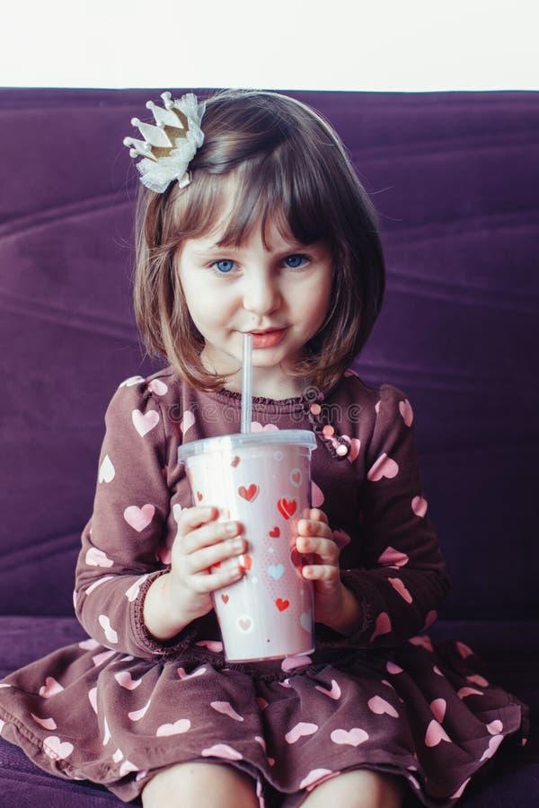 逗人喜爱的可爱的有心脏的女孩佩带的礼服和冠坐长沙发 库存图片