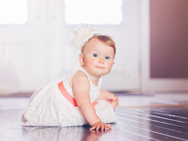 逗人喜爱的可爱的白肤金发的白种人微笑的小儿童女孩画象有蓝眼睛的在有红色弓的白色礼服坐地板 免版税库存图片