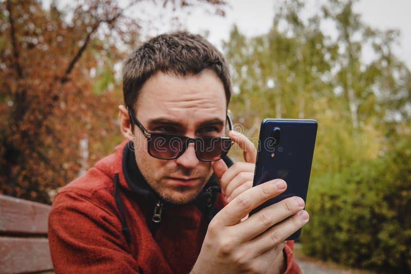 逗人喜爱的可爱的英俊的严肃的人佩带的便服和太阳镜在拿着智能手机读书sms之外 工作 免版税库存图片