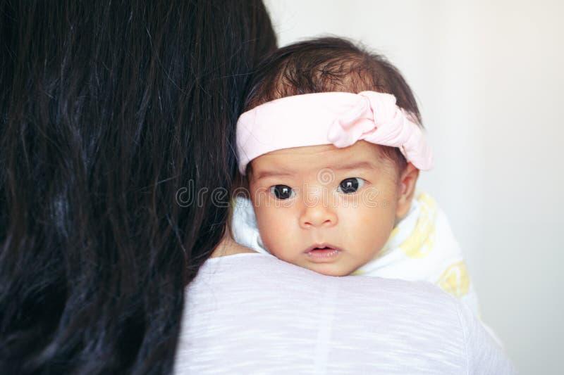 逗人喜爱的可爱的醒的亚裔中国混合的族种新生儿女孩特写镜头画象有说谎在父母肩膀的睁开眼睛的 免版税库存图片