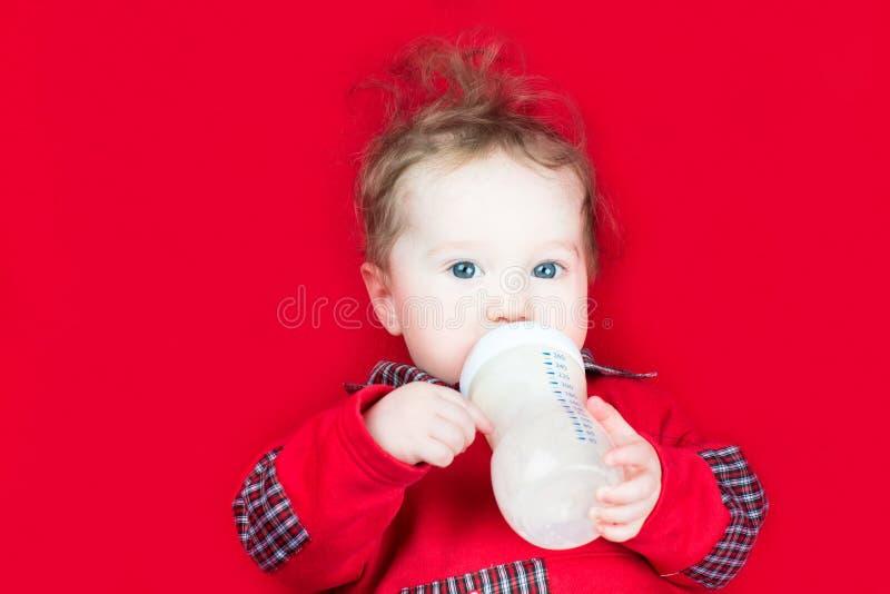 逗人喜爱的在一条红色毯子的婴孩饮用奶 免版税库存图片
