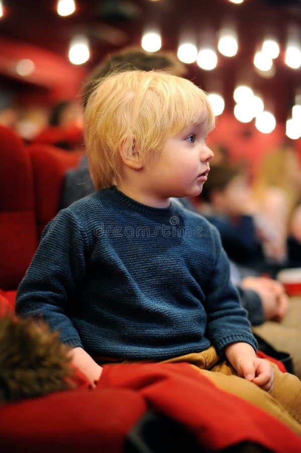 逗人喜爱的在戏院的小孩男孩观看的动画片电影 图库摄影
