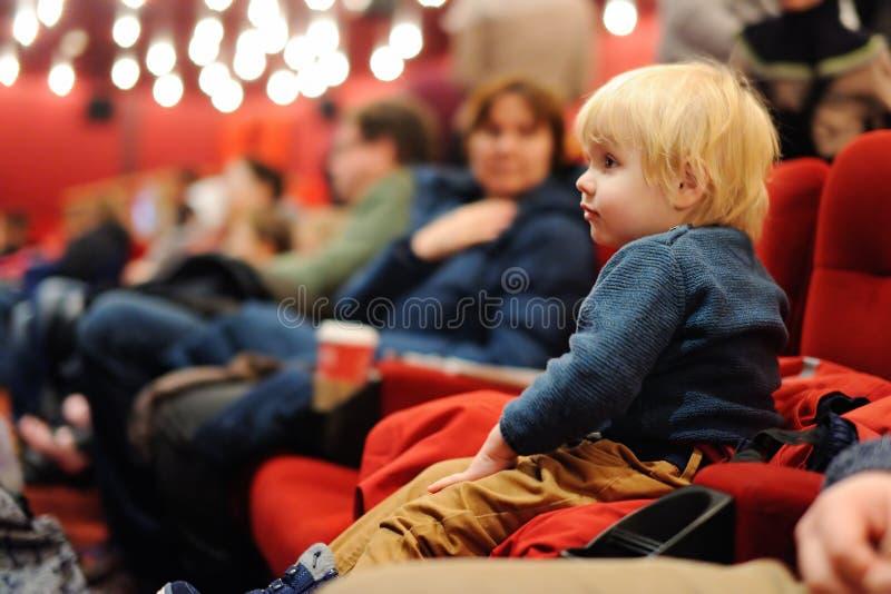 逗人喜爱的在戏院的小孩男孩观看的动画片电影 免版税库存照片