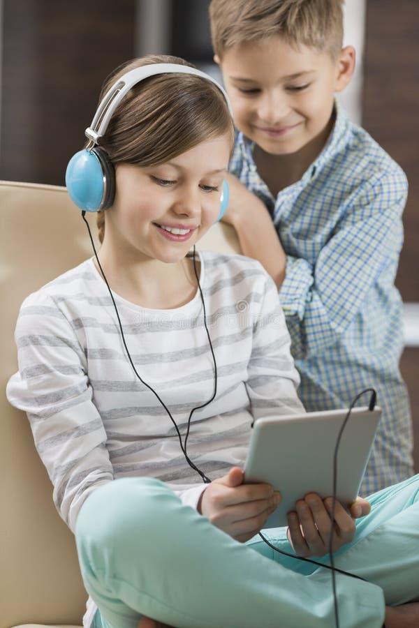 逗人喜爱的在数字式片剂的女孩听的音乐,当在家时站立在她后的兄弟 免版税库存照片