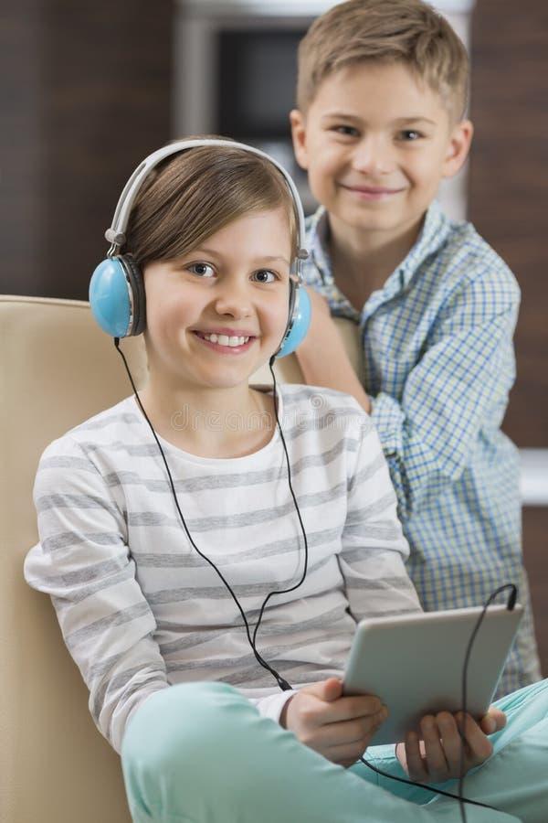 逗人喜爱的在数字式片剂的女孩听的音乐画象,当站立在她后时的兄弟 库存图片