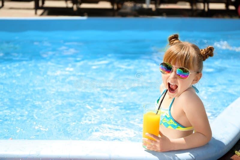 逗人喜爱的在游泳场的女孩饮用的汁液 库存图片