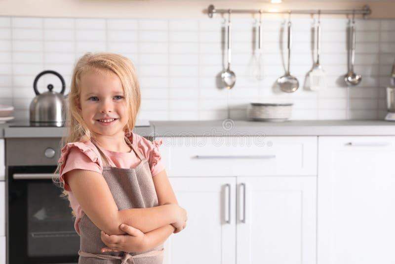 逗人喜爱的在烤箱附近的女孩佩带的围裙在厨房里 图库摄影