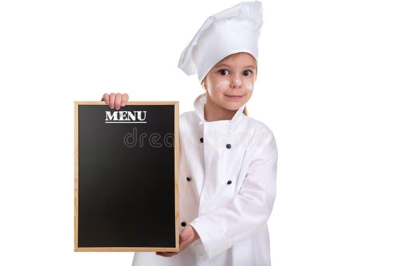 逗人喜爱的在白色背景隔绝的女孩厨师白色制服 有拿着菜单黑色空的委员会的一张被撒粉于的面孔的女孩 免版税库存图片