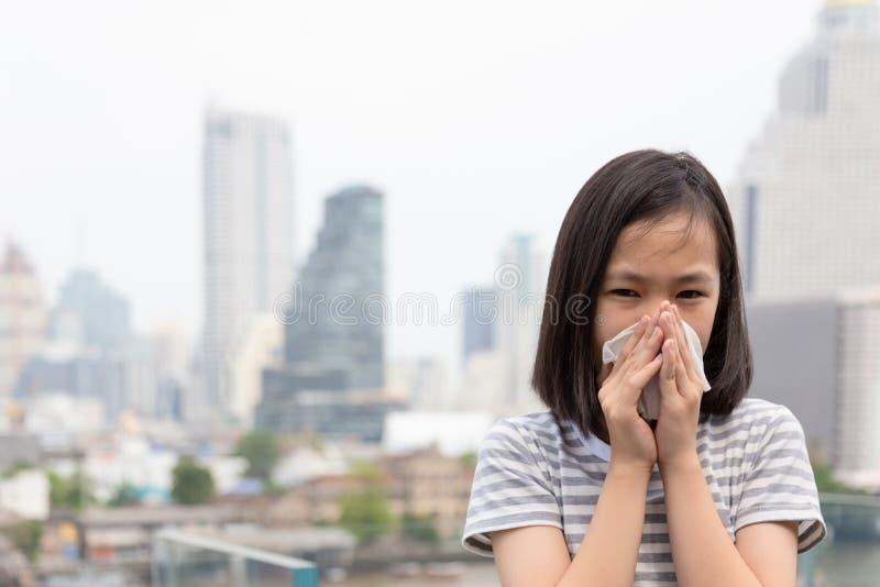 逗人喜爱的在纸手帕,打喷嚏在城市大厦的一个组织的亚裔孩子的女孩吹的鼻子画象  免版税库存照片