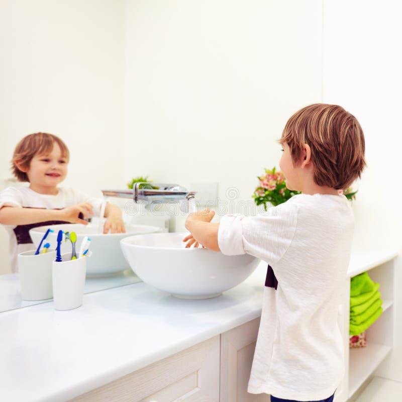 逗人喜爱的在自来水下的孩子洗涤的手在卫生间里 免版税图库摄影