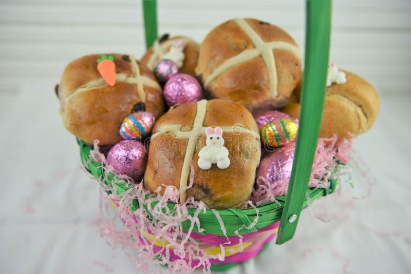 逗人喜爱的复活节篮子用新鲜的十字面包和复活节彩蛋填装了 库存照片